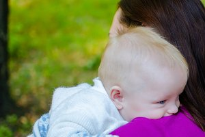 Mother hugs her baby in the park
