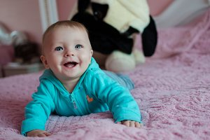 Smiling baby lying in parent's bed
