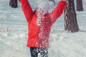 Happy girl throwing snow in the air on sunny day