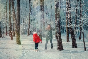 Children play in snowy forest.