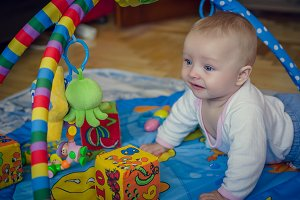 Baby boy crawling on colorful playmat