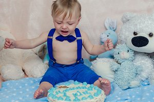 Baby boy crying while eating his birthday party cake