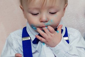 Funny baby is eating a tasty cake.