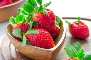 Wooden bowl with a luscious garden strawberries closeup, selecti