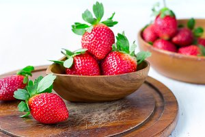 Ripe strawberry in the background bowl of berries, selective foc