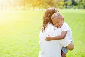 Mother of mixed African American boy carrying her kid in the park