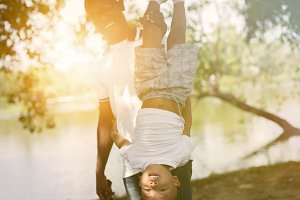 Dad holding a son upside down in park under sunlight
