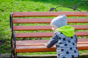 Toddler standing near the bench
