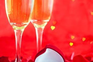 Valentines day background with champagne, ring and rose petals