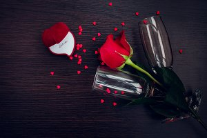 Red rose, ring, hearts and champagne glasses