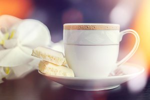 Tasty white porous chocolate and cup of coffee