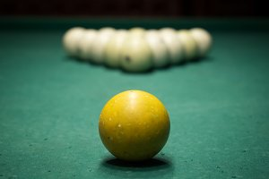 Billiard game. Old pool balls on light beam.