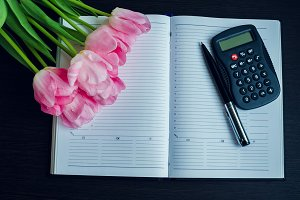 Tulips with pen and calculator on empty notebook