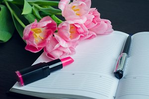 Tulips with pen and lipstick on empty notebook