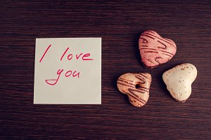Note I love you with cookies on wooden background