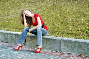 woman sit on a road kerb