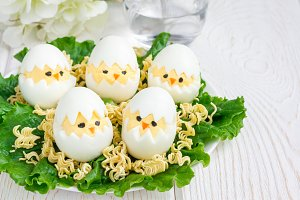 Little chicken in nest, deviled eggs served with salad and dry ramen on white plate, horizontal, copy space