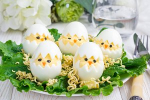 Little chicken in nest, deviled eggs served with salad and dry ramen on white plate, horizontal