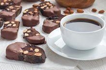 Homemade dark chocolate biscotti cookies with almonds, covered with melted chocolate, and cup of coffee, horizontal