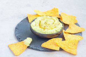 Healthy avocado hummus sprinkled with olive oil, paprika and sesame, served with nachos, horizontal