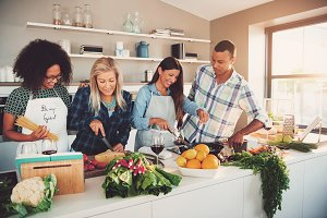 Four mixed friends preparing a meal in kitchen