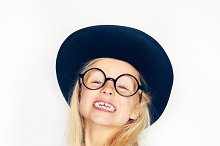 Smiling little girl in hat and glasses