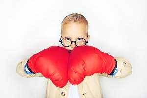 Boy in boxing gloves looking at camera