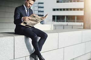 Man wearing suit sitting and reading newspaper