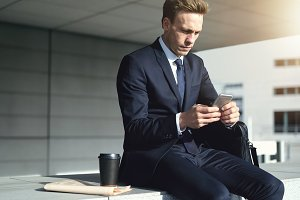 Young stylish businessman while using his phone