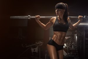 Fit young woman lifting barbells