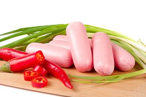 sausages with green onions and chilli on a cutting board isolated  white background closeup
