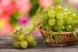 green grapes in a wicker basket on  wooden table with  blurred background