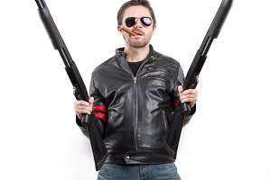 Man in leather jacket with shotguns