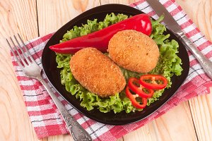two fried breaded cutlet with lettuce on a black plate and wooden background