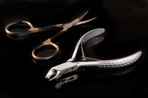 nail scissors and clippers to remove the cuticle care products on black background