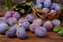 plum in a wicker basket on the wooden background