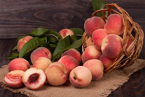 peaches in a wicker basket with leaves on wooden table
