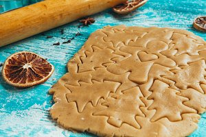Gingerbread dough with molds for baking cinnamon on blue wooden table