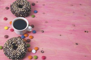 Cup of coffee and donuts on wood