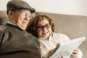 Grandpa and grandson reading a news.