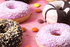 assortment of donuts and candies on pink wooden background