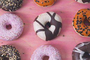 assortment of donuts on pink wooden