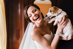 Pretty bride plays with a dog