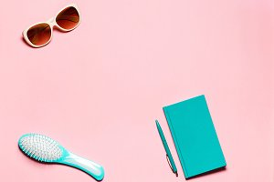 Minimalistic composition of hairbrush and eyeglasses on pink copy space