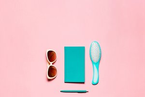 Feminine accessory of hairbrush, glasses, diary and pen isolated on pink copy space.