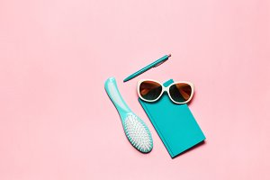 Flat minimalistic feminine composition of turquoise accessory: hairbrush, glasses, diary and pen isolated on pink copy space background.