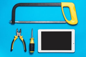 White Tablet and set of yellow construction tools to repair on a blue table: saw, screwdriver, pliers. Top view. Mechanic workspace.
