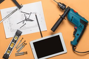 Set of construction tools to repair and white tablet on orange-brown table: drill, hammer, pliers, self-tapping screws, roulette, level, drawing, pencil. Top view