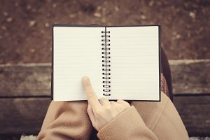 Woman's hands holding a notebook.
