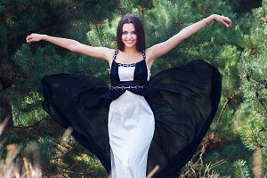 Graceful charming brunette model posing in black dress in coniferous park